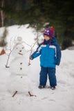 做雪人的逗人喜爱的男孩 库存照片