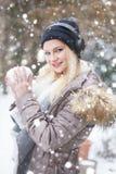 做雪球和听的音乐在snowfa的年轻白肤金发的妇女 库存图片