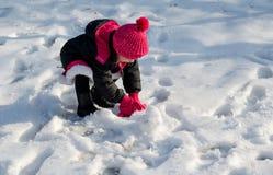 做雪球的小女孩 免版税库存图片