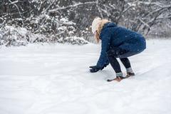做雪球的年轻女人外面在一多雪的天 免版税库存照片
