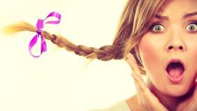 做震惊面孔的辫子头发的十几岁的女孩 库存图片