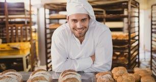做面包的愉快的小企业主人 免版税图库摄影