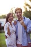 做面孔和手指姿态的年轻夫妇 免版税库存照片