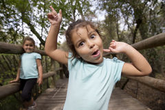 做面孔和打手势在照相机的T恤杉的滑稽的女孩 免版税库存照片