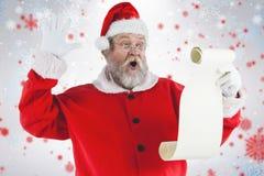 做面孔的惊奇的圣诞老人的综合图象,当读纸卷时 免版税图库摄影