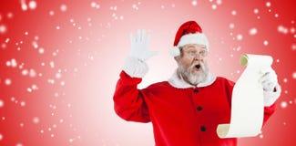 做面孔的惊奇的圣诞老人的综合图象,当读纸卷时 免版税库存图片