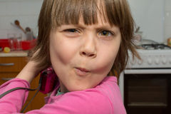 做面孔的美丽的矮小的女孩 图库摄影