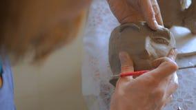 做面孔的陶瓷工在有特定工具的黏土杯子在瓦器车间 影视素材
