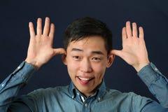做面孔的滑稽的年轻亚裔人 免版税库存照片