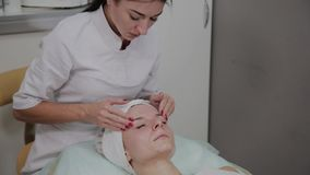 做面部按摩的专业美容师在美容院里 股票录像