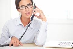 做顾客服务的拉丁秘书在办公室 免版税库存照片
