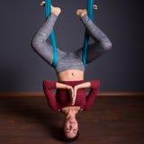 做飞行瑜伽的年轻美丽的深色的妇女 坐在hammoc 库存图片