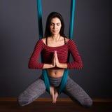 做飞行瑜伽的年轻美丽的深色的妇女 坐在hammoc 库存照片
