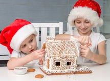 做饼干房子的圣诞老人帽子的两个妹 免版税库存图片