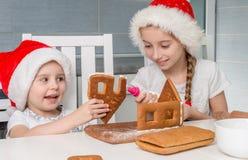 做饼干房子的圣诞老人帽子的两个妹 免版税图库摄影