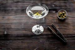 做马蒂尼鸡尾酒鸡尾酒 玻璃用饮料、橄榄和器物在黑暗的木背景顶视图copyspace 免版税图库摄影