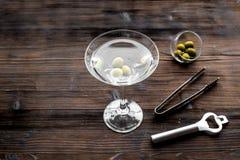 做马蒂尼鸡尾酒鸡尾酒 玻璃用饮料、橄榄和器物在黑暗的木背景顶视图copyspace 免版税库存照片