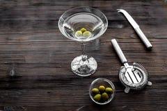 做马蒂尼鸡尾酒鸡尾酒 玻璃用饮料、橄榄和器物在黑暗的木背景顶视图copyspace 免版税库存图片
