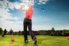 做高尔夫球摇摆的路线的年轻高尔夫球运动员 图库摄影