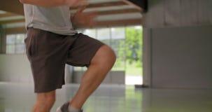 做高膝盖的年轻成人人跳跃锻炼在健身体育锻炼期间 在腿的细节 难看的东西工业都市 影视素材