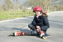 做鬼脸在痛苦中的年轻可爱的少年溜冰者在采取a以后 库存照片