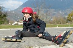 做鬼脸在痛苦中的年轻可爱的少年溜冰者在采取a以后 免版税库存照片