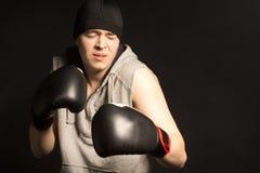 做鬼脸在痛苦中的年轻拳击手 库存图片