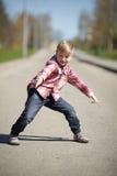 做鬼脸在街道上的小男孩在4月 免版税库存图片