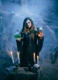 做魔术的可爱的巫婆在不可思议的穴 免版税库存图片