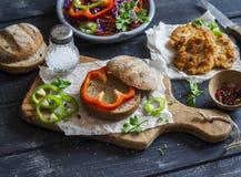 做鱼汉堡的成份-黑麦小圆面包、红叶卷心菜、胡椒、红萝卜、草本和酥脆油煎的鱼炸肉排在黑暗的木ba 图库摄影