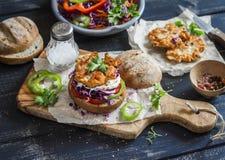 做鱼汉堡 成份-黑麦小圆面包、红叶卷心菜、胡椒、红萝卜、草本和酥脆油煎的鱼炸肉排在黑暗的木后面 免版税库存图片