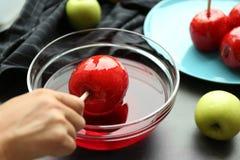做鲜美焦糖苹果的女性 免版税库存图片