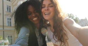 做鸭子面孔的两愉快的多文化gilrfriends Selfie,亲吻在面颊,当走街道时 股票视频