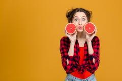 做鸭子面对和举行两个一半葡萄柚的妇女 图库摄影