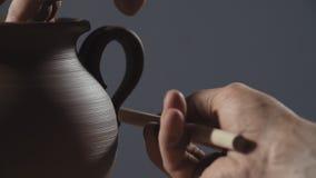 做黏土产品的人手 陶瓷工由在慢动作的黏土做水罐把柄 股票录像