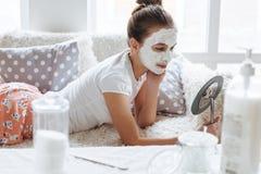 做黏土脸面护理面具的女孩 免版税库存图片