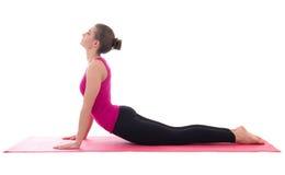 做年轻亭亭玉立的妇女舒展在被隔绝的瑜伽席子的锻炼 图库摄影