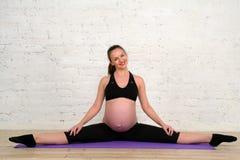 做年轻人的孕妇舒展麻线在瑜伽席子行使 图库摄影