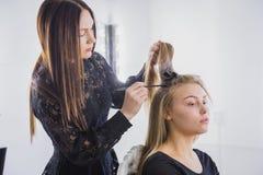 做年轻俏丽的妇女的专业美发师发型有长的头发的 免版税库存照片