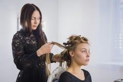 做年轻俏丽的妇女的专业美发师发型有长的头发的 库存照片