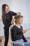 做年轻俏丽的妇女的专业美发师发型有长的头发的 免版税图库摄影