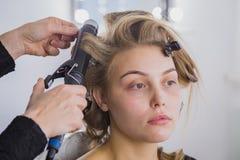 做年轻俏丽的妇女的专业美发师发型-做卷曲 库存图片