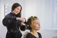 做年轻俏丽的妇女的专业美发师发型-做卷曲 免版税库存图片