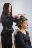 做年轻俏丽的妇女的专业美发师发型-做卷曲 免版税库存照片