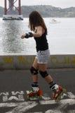 做滑冰的女孩在城市 免版税库存图片