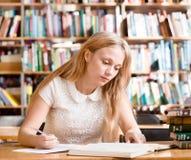 做任务的年轻女学生在图书馆里 免版税图库摄影