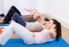 做仰卧起坐的人们在健身房 库存图片