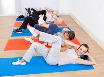 做仰卧起坐的人们在健身房 库存照片