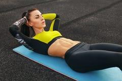 做仰卧起坐的健身妇女在解决的体育场内 行使abdominals的运动的女孩,室外 免版税库存图片