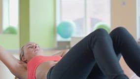 做仰卧起坐的妇女在健身房 影视素材